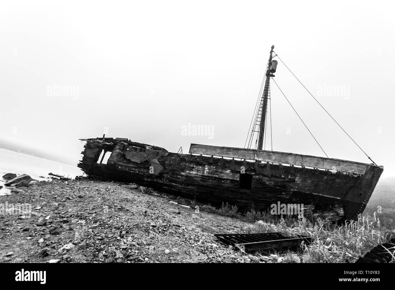 Old wooden wrecked ship in the morning fog. Black and white image - Stock Image