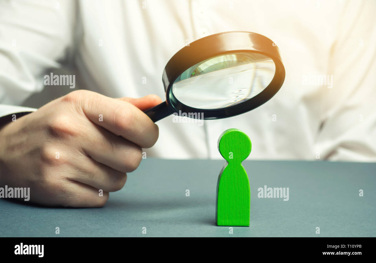 A businessman is holding a magnifying glass over a green man figure. Search for a talented employee. Identifying strengths in the company. Disclosure  - Stock Image