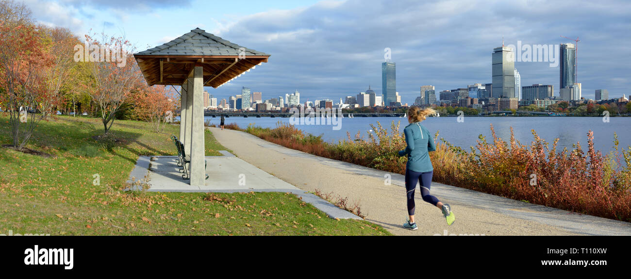 Boston pano in the fall. People walking and running on Charles River bank path, Back Bay city skyline in the background - Stock Image