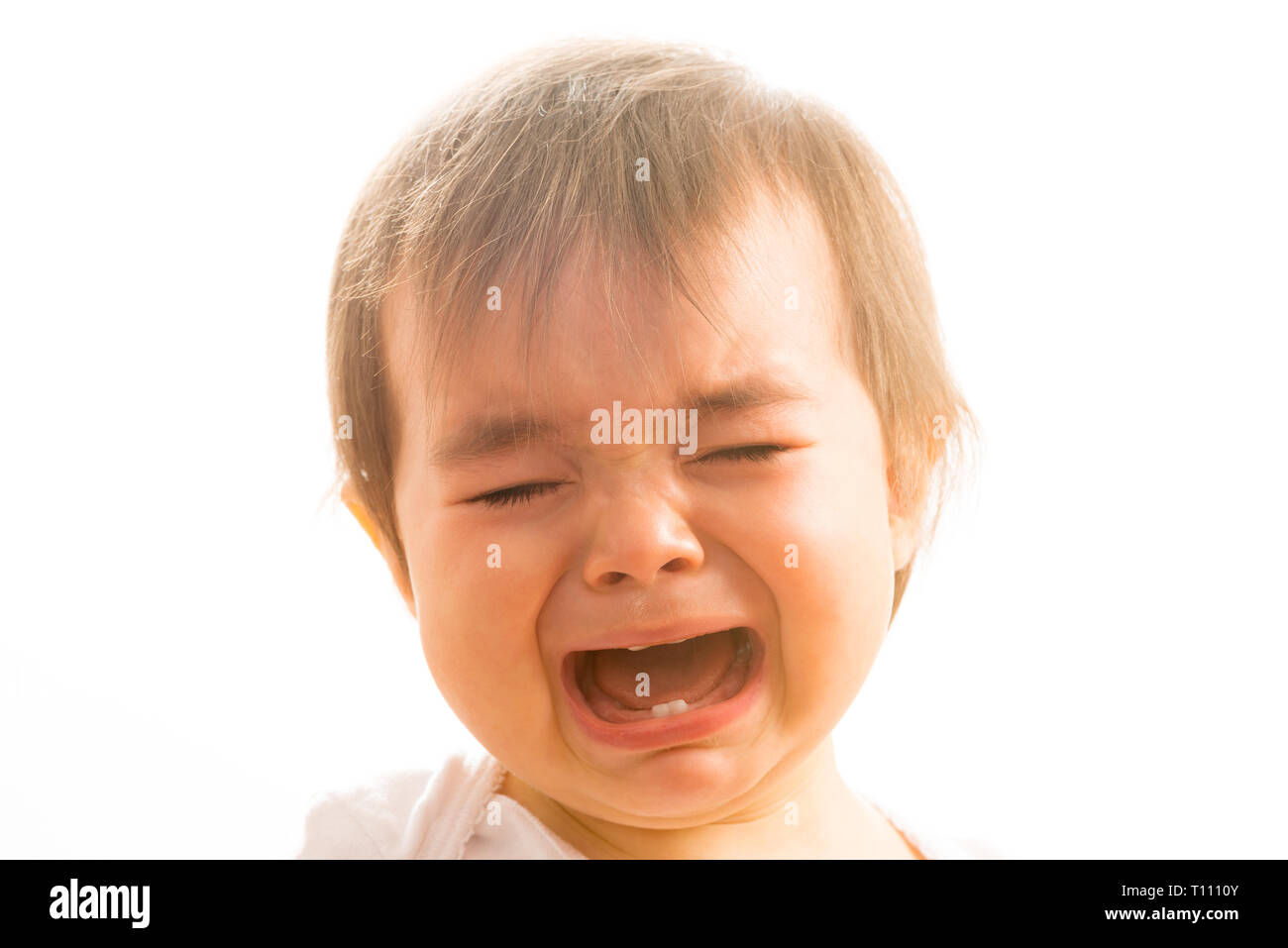 Close up of a 1 year old baby girl crying - Stock Image