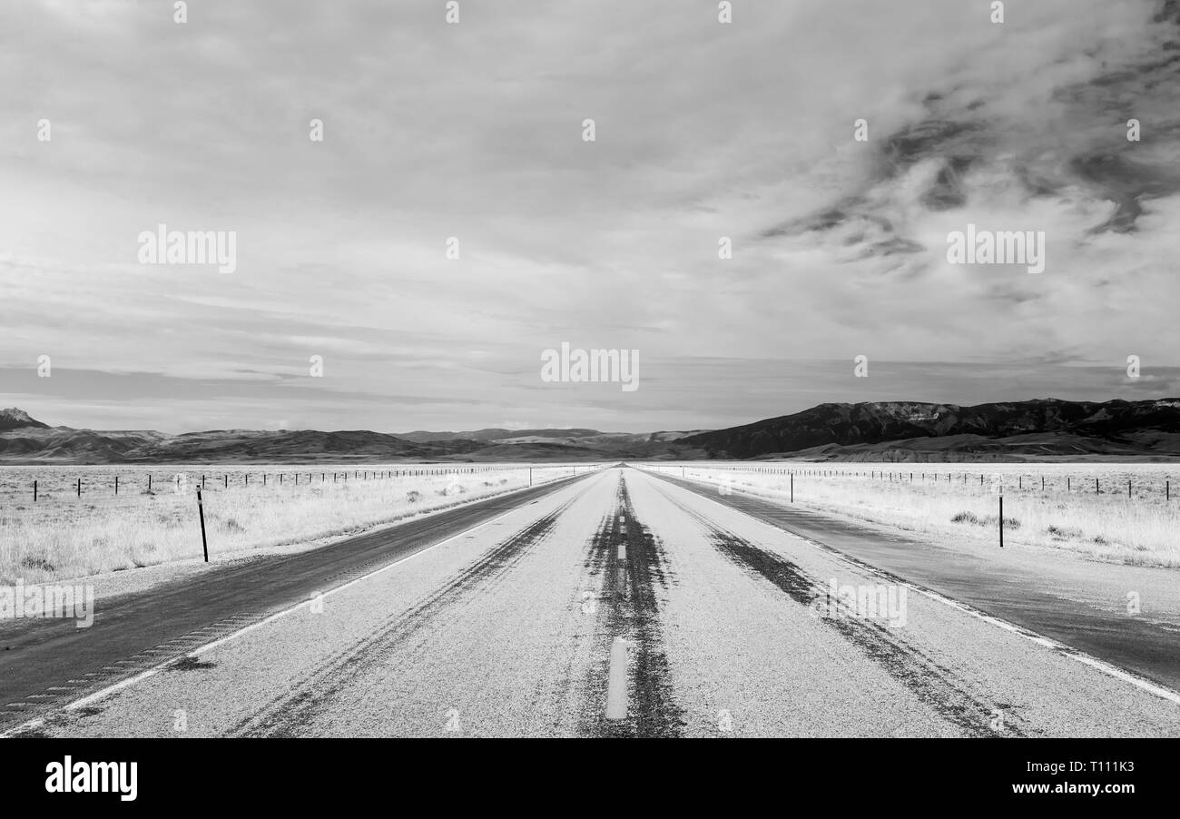 Interstate 90 flanked by prairie and the Rockies on a hot summer morning in Montana, USA. - Stock Image