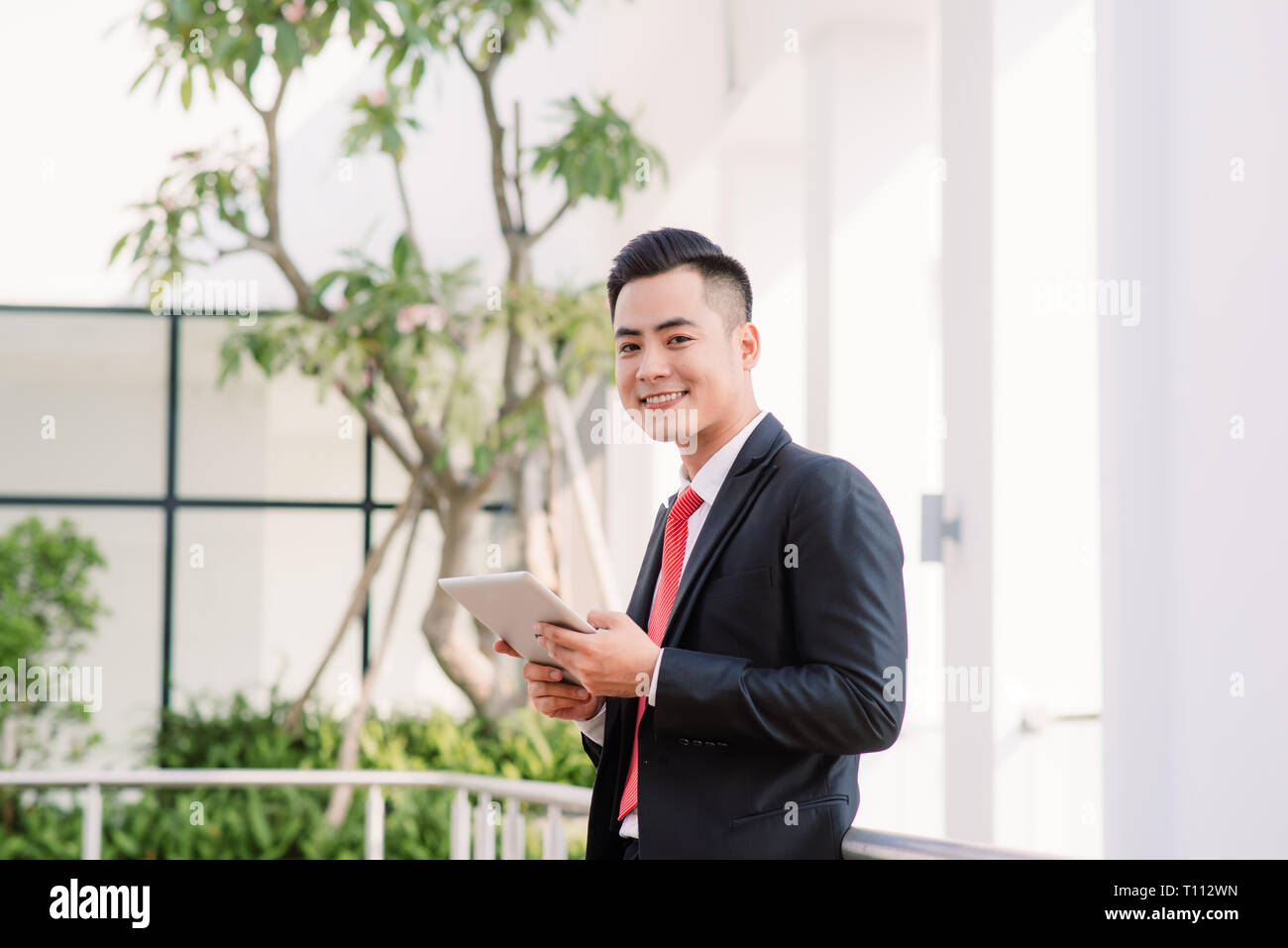 Young Asian Businessman working on tablet, Lifestyle of modern male to communicate, message or use technology in business, Always connected concept, F - Stock Image