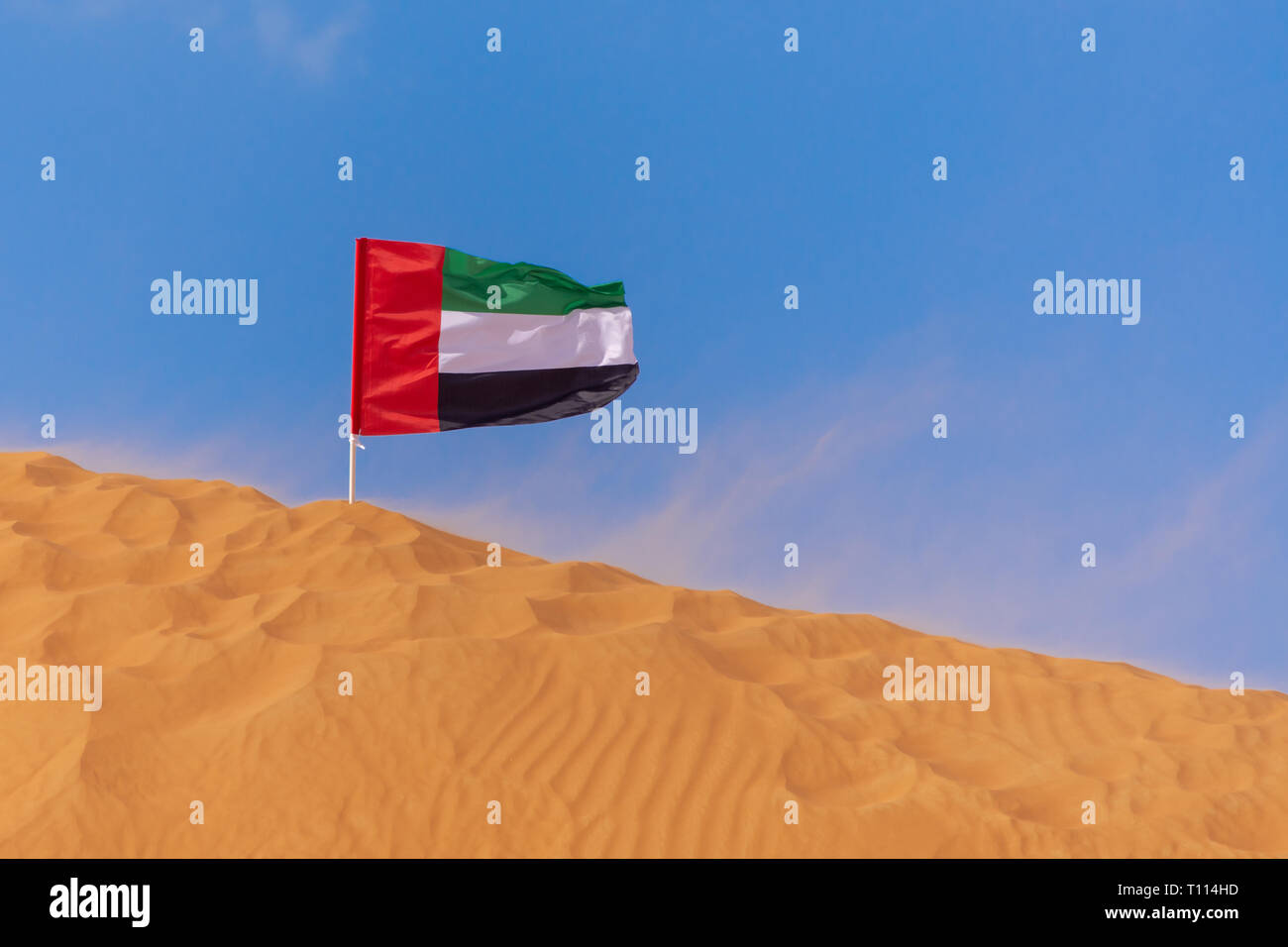 UAE Flag blowing in the wind on the top of an orange sand dune in the blue sky in Ras al Khaimah, United Arab Emirates. Stock Photo