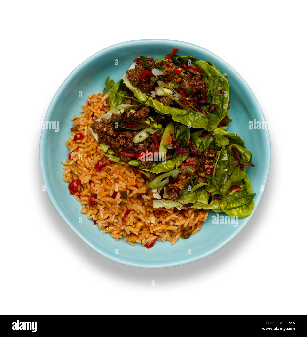 A bowl of succulent Spicy Beef Lettus Wraps on a bed of rice isolated on a white background with a drop shadow. - Stock Image