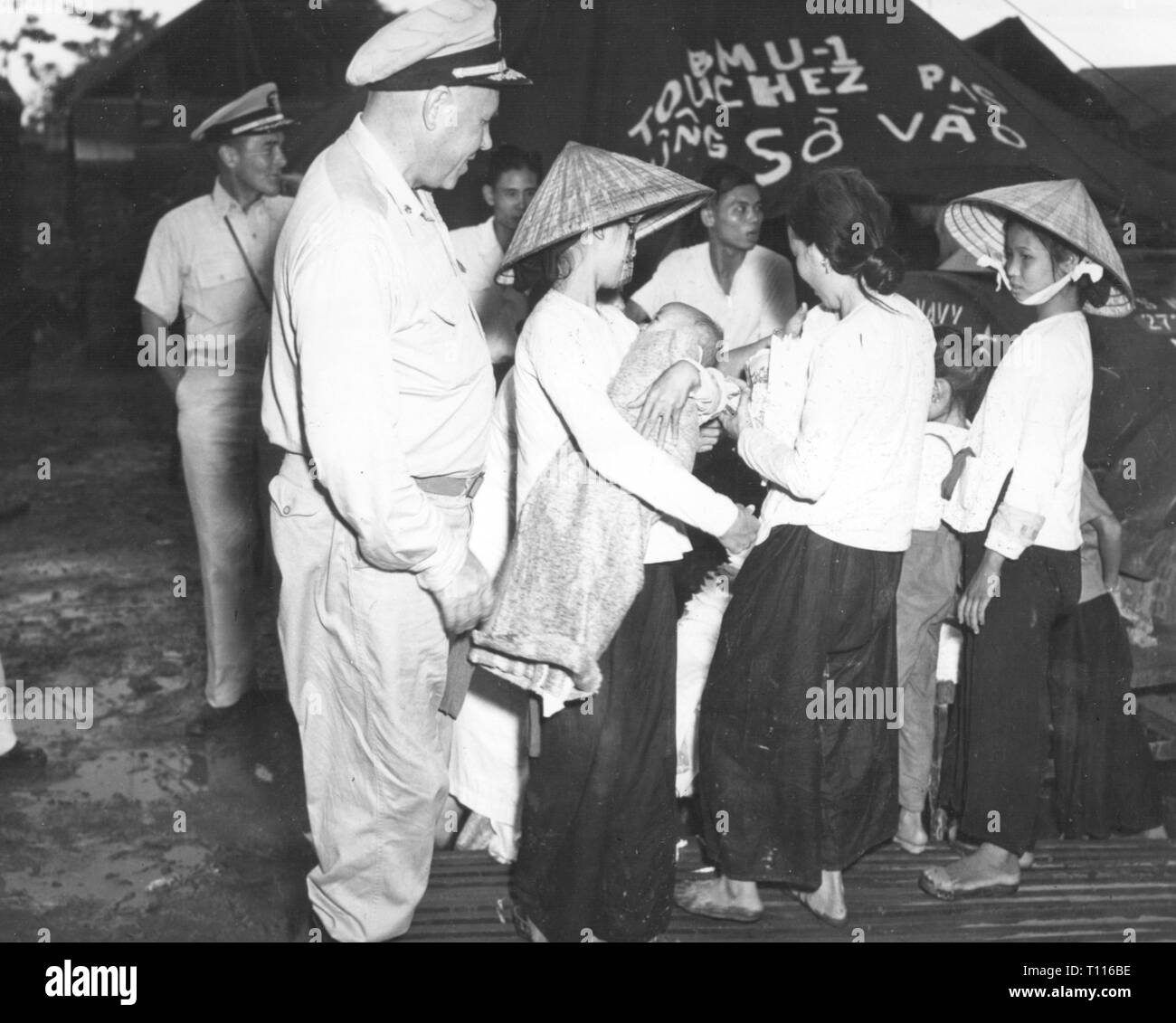 Indochina War 1946 - 1954, mass evacuation of Vietnamese civilians from Haiphong to Saigon, September 1957, captain Julius Amberson, chief of the preventive medicine division at the Naval Hospital in Bethesda, Maryland, is inspecting a refugee camp, navy physician, physician, physicians, medical care, US navy, medical service, first aid, United States Navy Medical Corps, USA, United States of America, American, women, evacuation, evacuations, flight, misery, hardship, people, war, wars, Indochina, Viet Nam, Vietnam, 20th century, 1950s, civilian,, Additional-Rights-Clearance-Info-Not-Available - Stock Image
