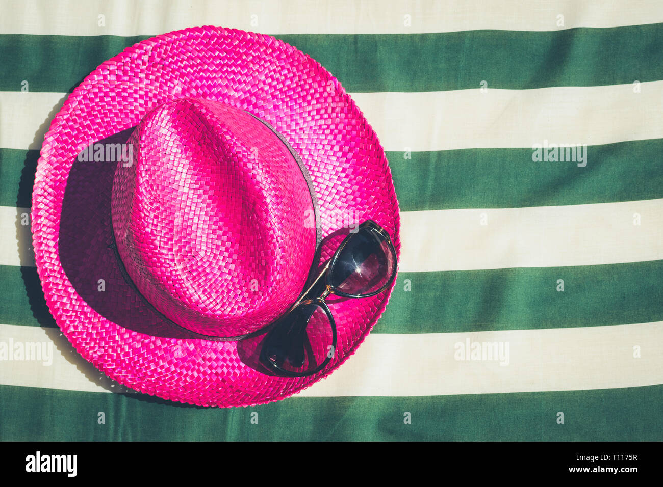 4763d080 Colorful holiday background with pink straw beach hat with sunglasses on  striped sunbed. Summer vacation