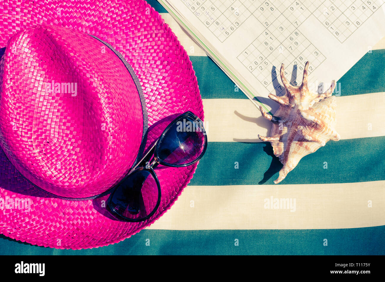 d02eb2ec Colorful holiday background with pink straw beach hat with sunglasses and  sudoku on striped sunbed.