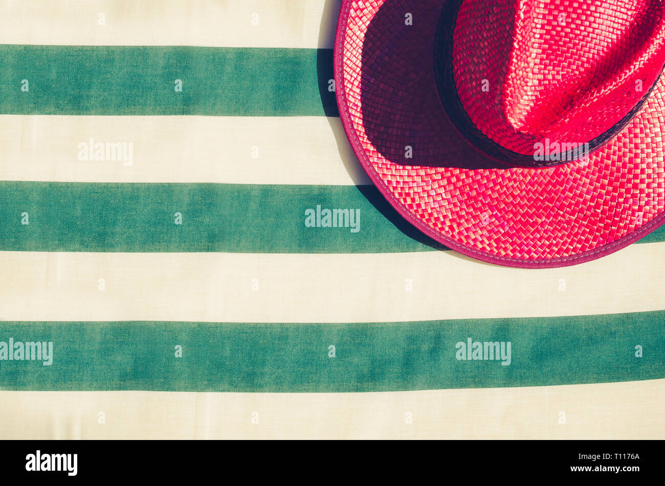 52632fa4 Colorful holiday background with red straw beach hat on striped sunbed.  Summer vacation concept.
