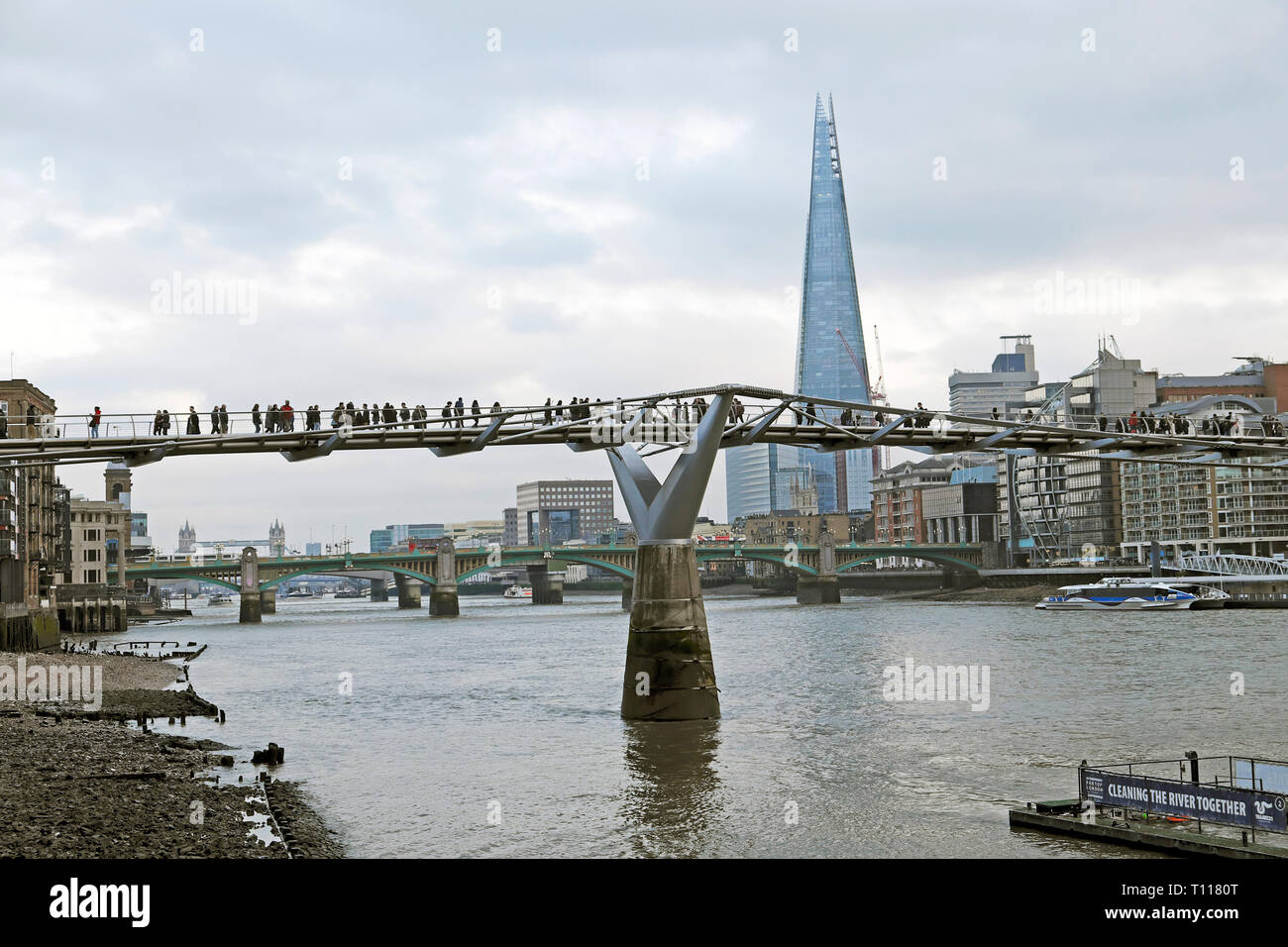 A view of the Shard building South Bank, London cityscape and people walking on the Millennium Bridge over the River Thames in winter UK KATHY DEWITT - Stock Image