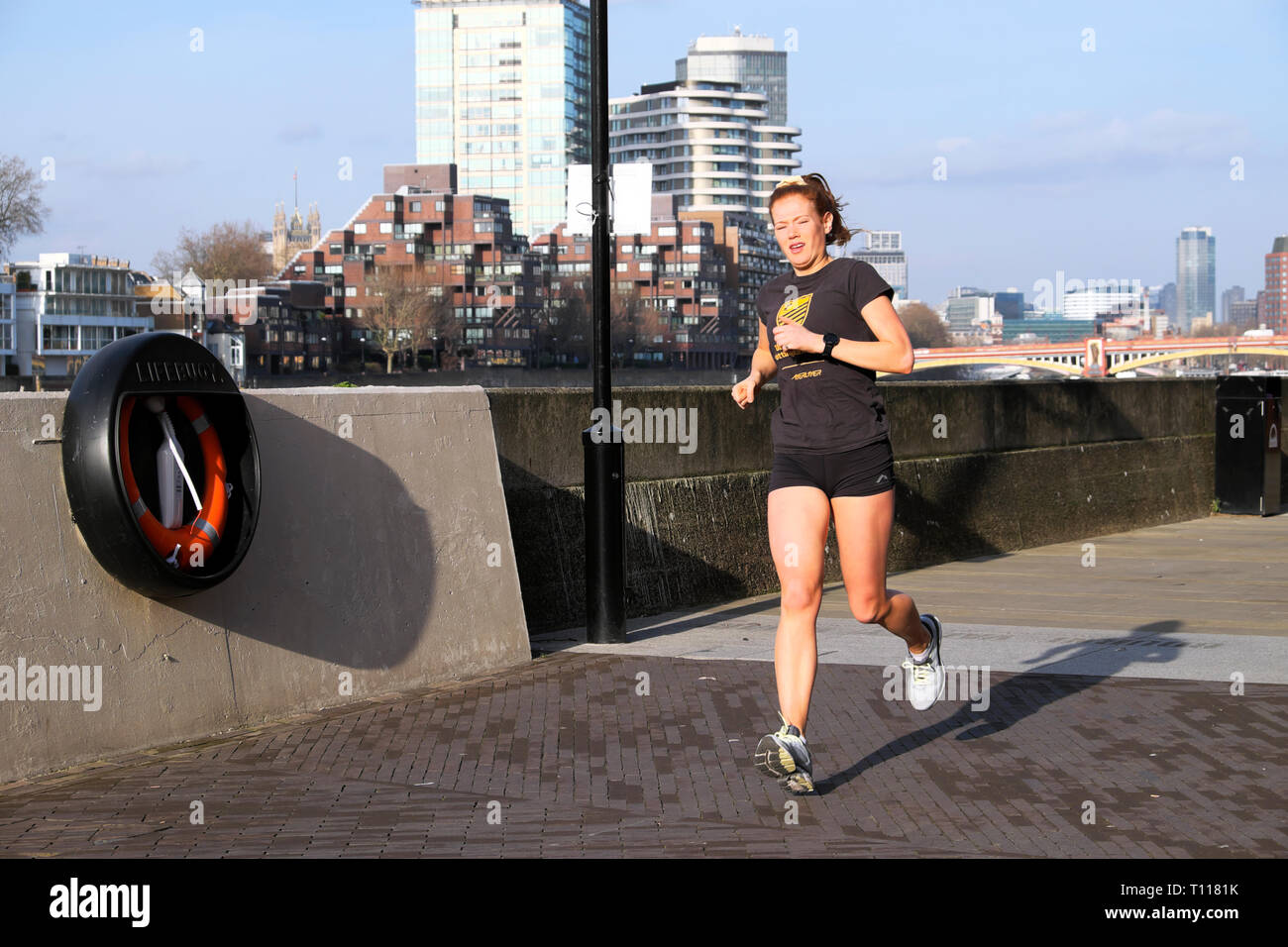 A young woman running by the River Thames in Battersea Wandsworth London England UK  KATHY DEWITT Stock Photo