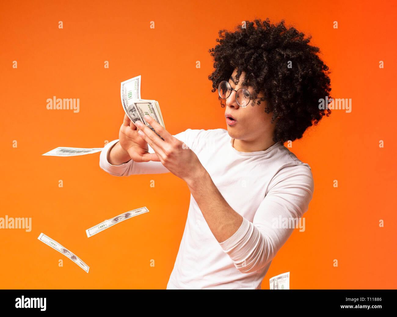 Happy young man throwing out money banknotes - Stock Image