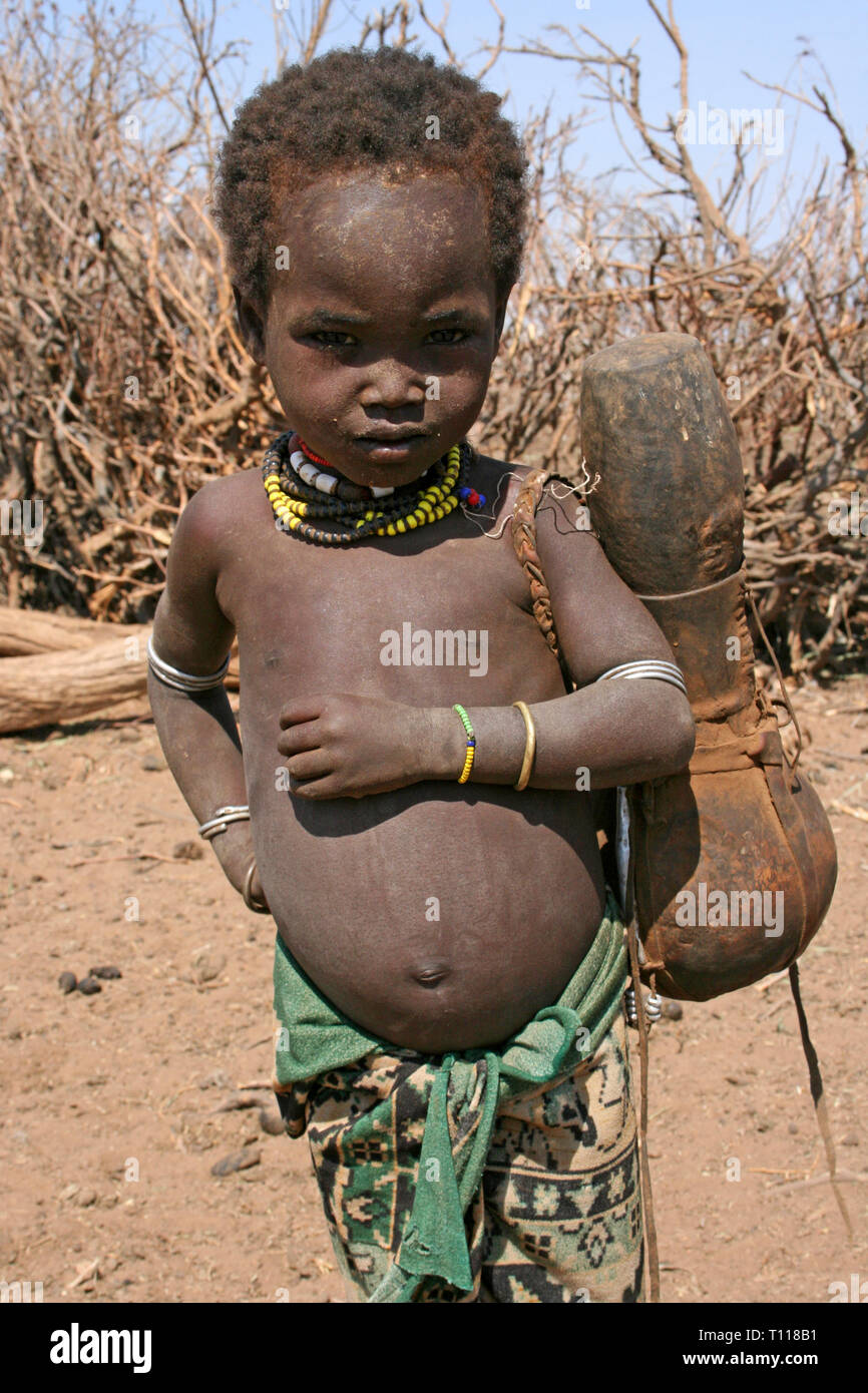 Arbore Tribe Boy Carrying Gourd, Omo Valley, Ethiopia - Stock Image