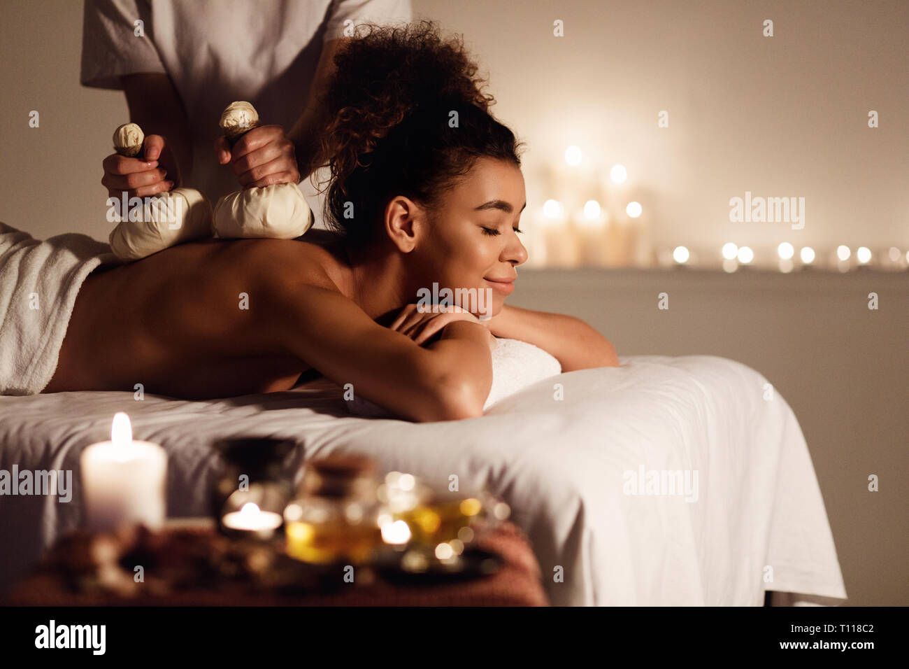 Woman enjoying back herbal massage and aroma therapy - Stock Image