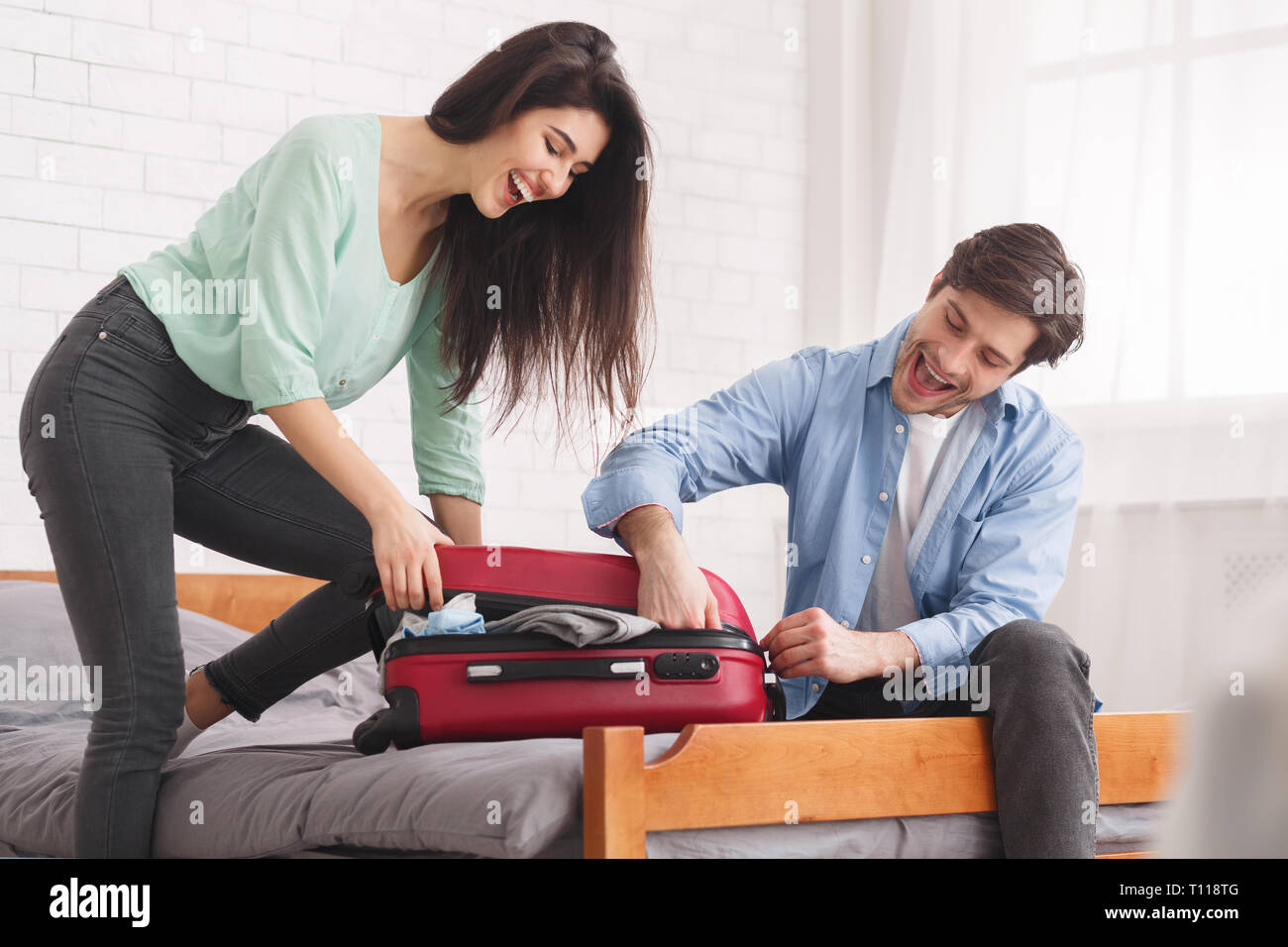 Couple trying to close full suitcase in bedroom Stock Photo