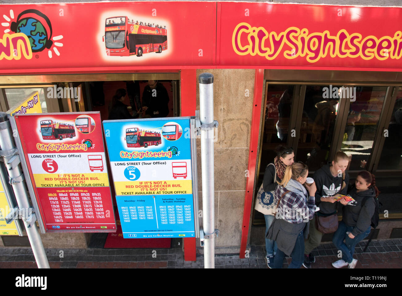 Tourists wait for the City Sightseeing tour bus at a bus stop in downtown Cape Town, South Africa. - Stock Image