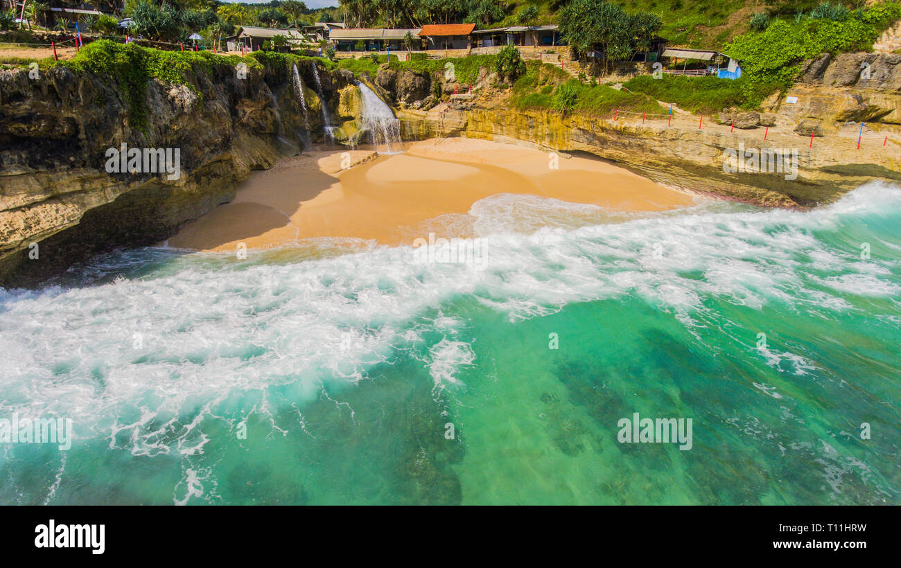 When freshwater meet salt water. A small waterfall, Banyu Tibo plunge into the sea in East Java - Stock Image