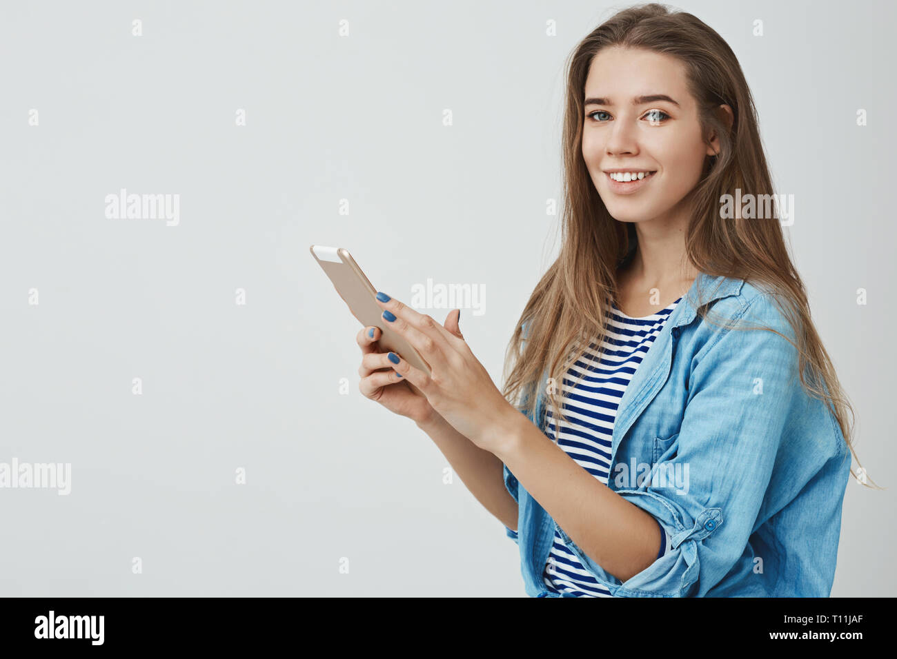 Studio shot charming feminine modern young 25s european woman long healthy hair holding digital tablet turning carefree delighted smile camera Stock Photo