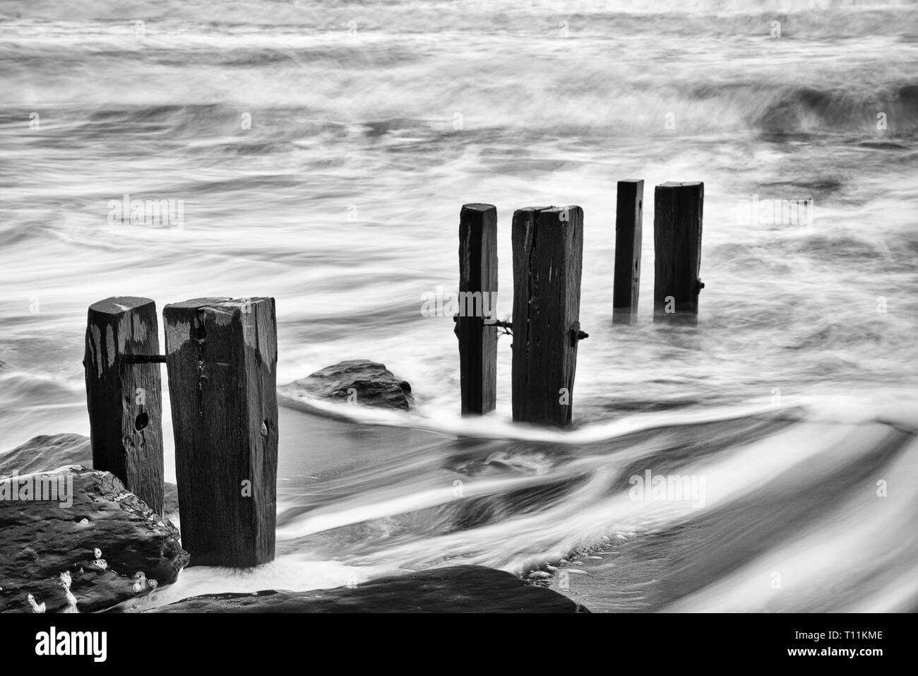 A rough incoming tide breaks against groynes and rocks - Stock Image