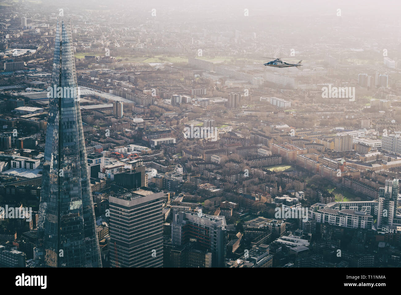 AW109 charter helicopter flying over London during an aerial photoshoot. - Stock Image