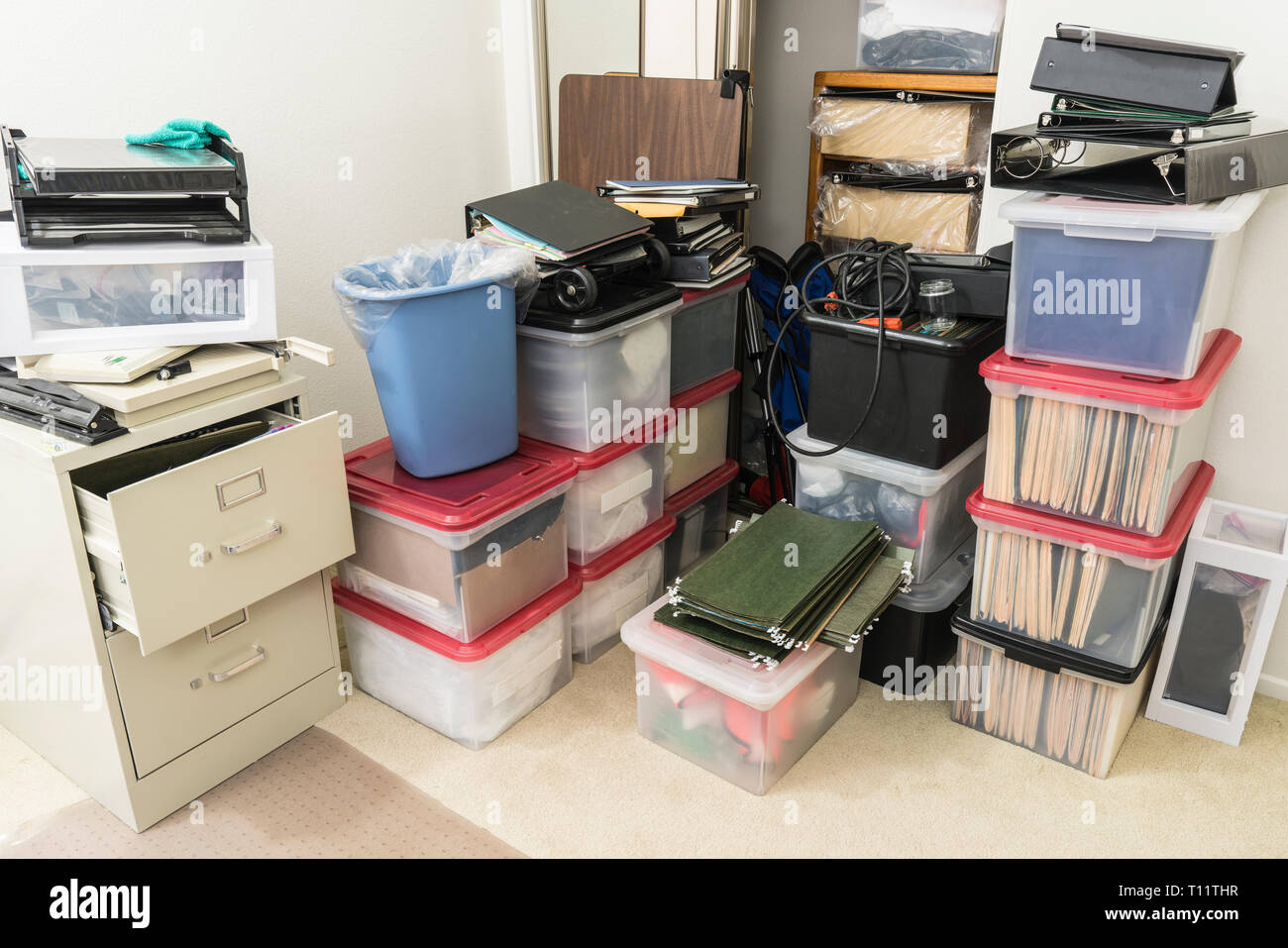 Cluttered corner with storage boxes, binders and miscellaneous office supplies. - Stock Image