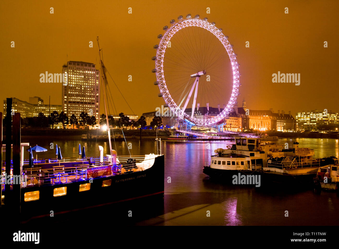 Great Britain, England, London.  The London Eye on the bank of the River Thames. The orange color is an effect of light pollution. - Stock Image