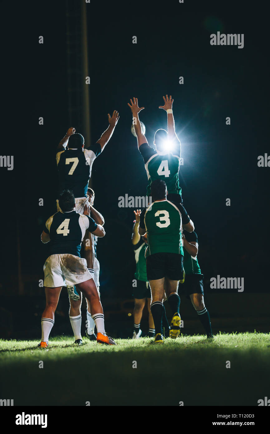 Rugby players jumping for line out at the stadium. Teams jumping for possession of the ball during rugby match. - Stock Image