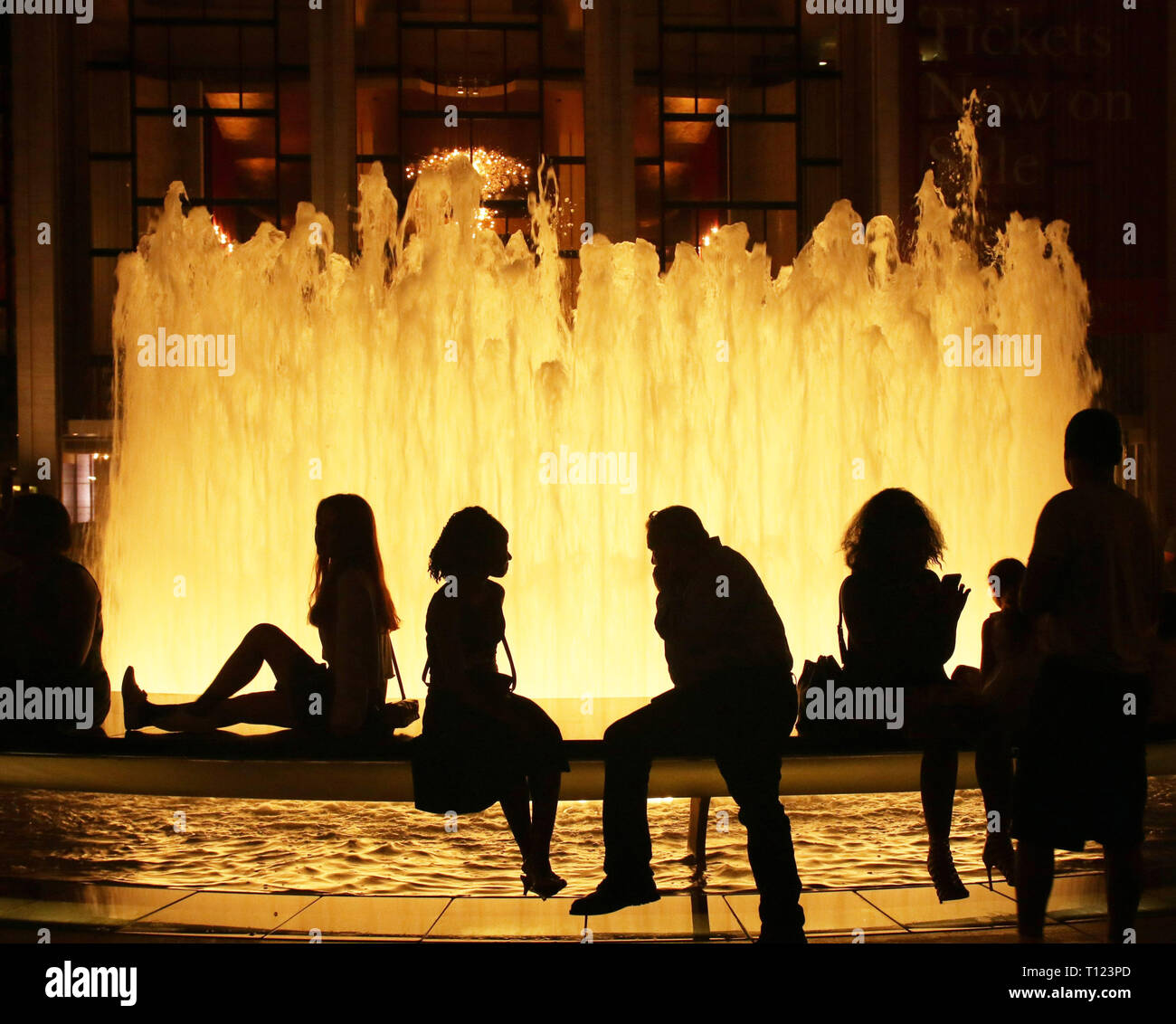 People sitting at the fountain at Lincoln Center, NYC, at night - Stock Image