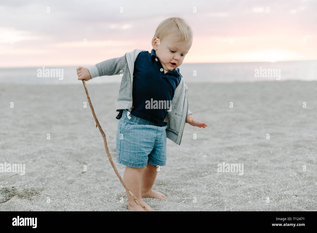 877306999 Portrait of Cute Little Baby Boy Child Playing and Exploring in the Sand at  the Beach During Sunset Outside on Vacation in Hoodie Zip-Up Sweat Shirt