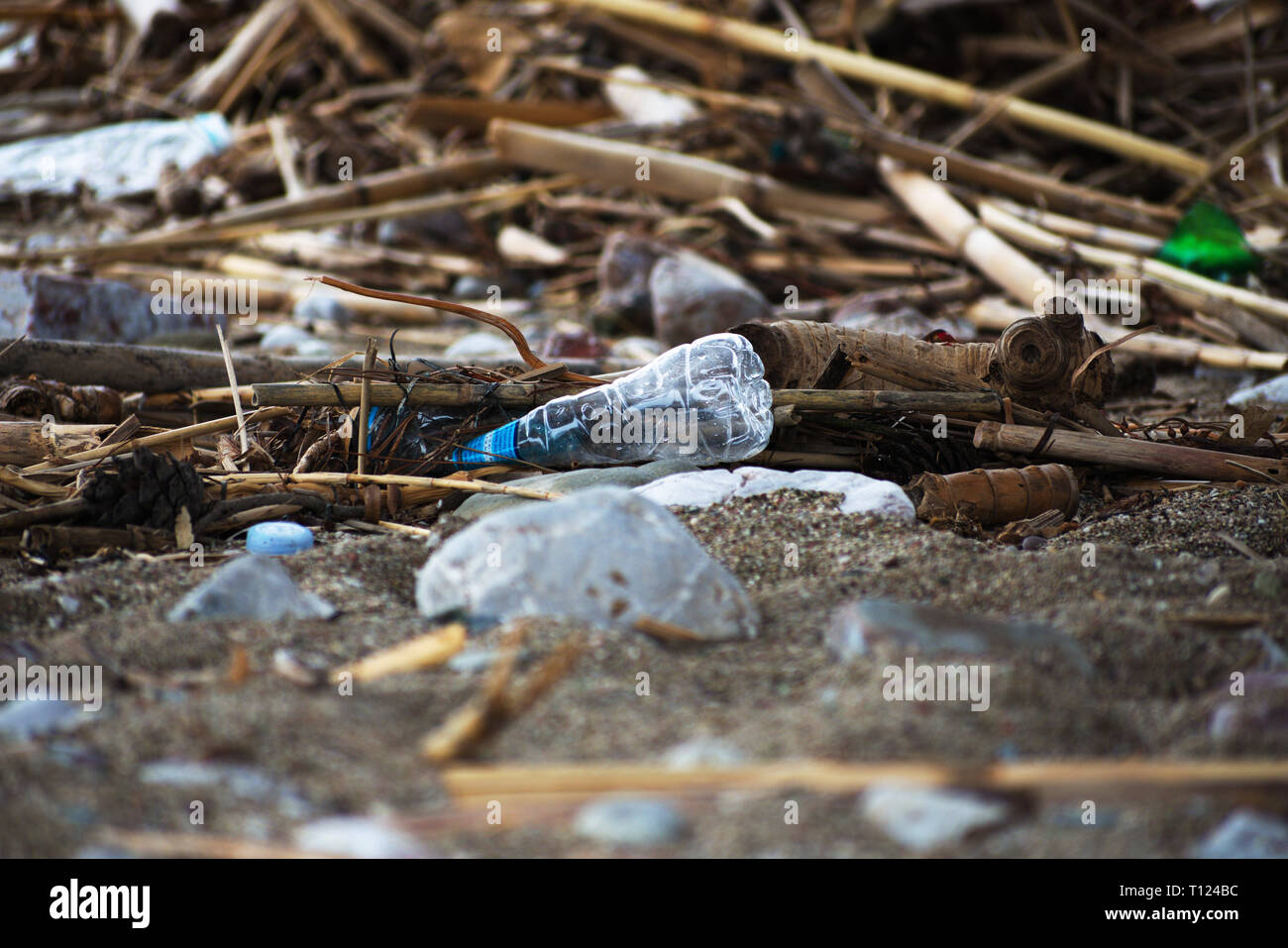 Spilled garbage on the beach.Empty used plastic bottle. - Stock Image