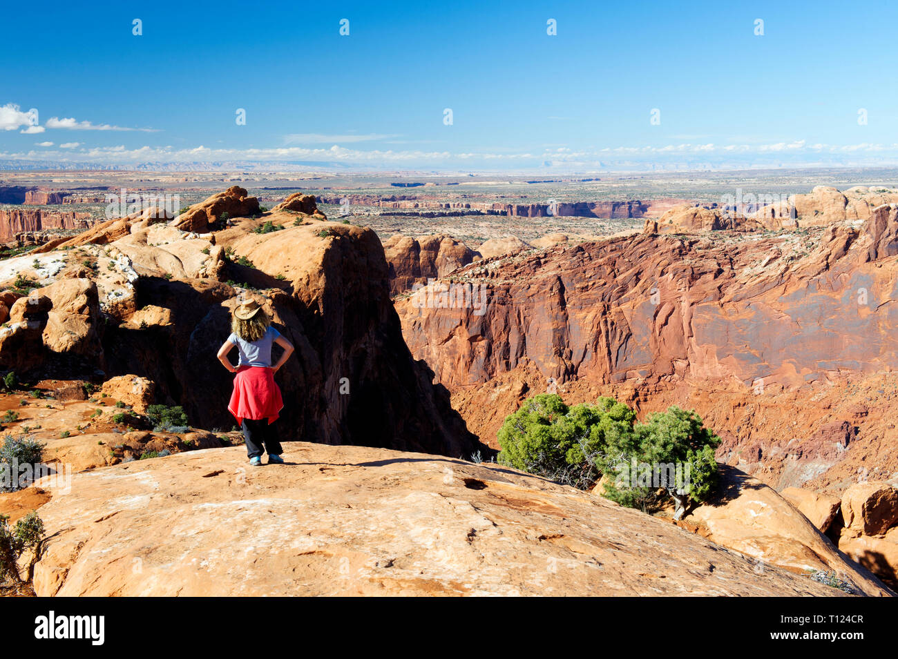 Female hiker contemplating the arid landscape of Canyonlands from the Upheaval Dome trail, Utah. - Stock Image