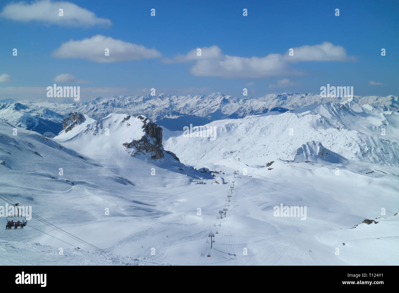 Alpine snowy peaks panoramic view with chair lifts, downhill ski slopes in 3 Valleys winter sport resort, Alps, France, on a sunny cold day . - Stock Image