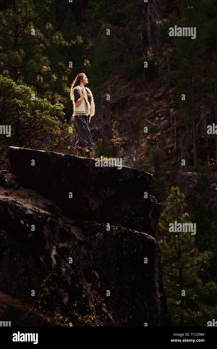 A confident and adventurous young woman wearing a skirt, vest and boots exploring the Sierra Nevada Mountains of Northern California alone. - Stock Image
