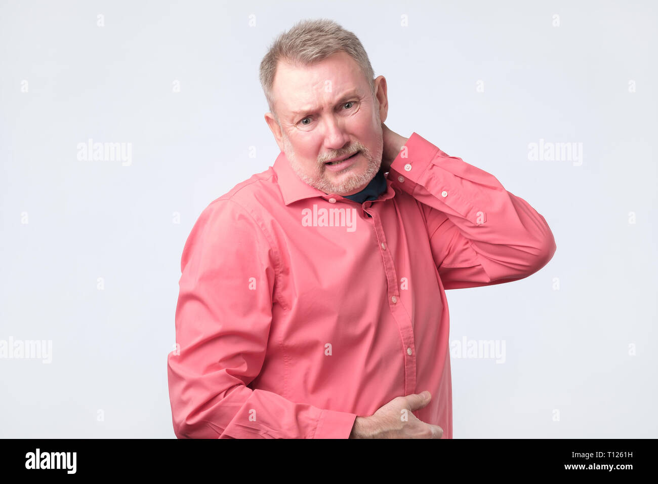 I need a massage. Frustrated senior man in red shirt holding hand on his neck. Studio shoot. - Stock Image