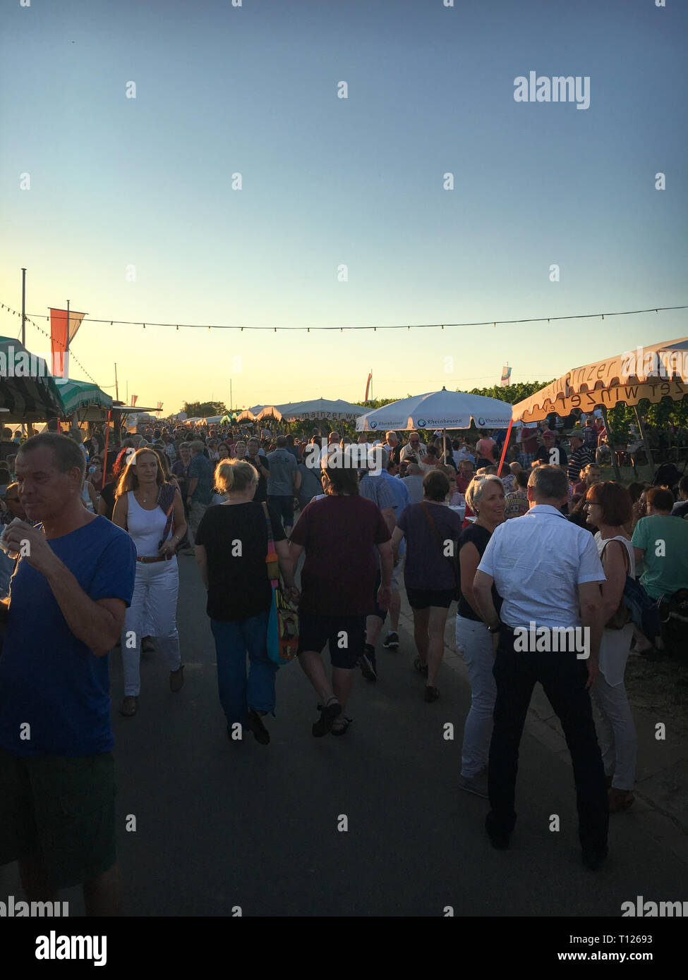 """Mainz, Germany – June 29, 2018: People enjoying food, wine and drinks at a local fair called """"Weinfest im Kirchenstück"""", a wine festival in Hechtsheim - Stock Image"""