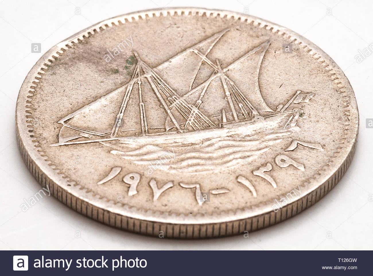 An old silver colored Kuwati dinar coin - Stock Image