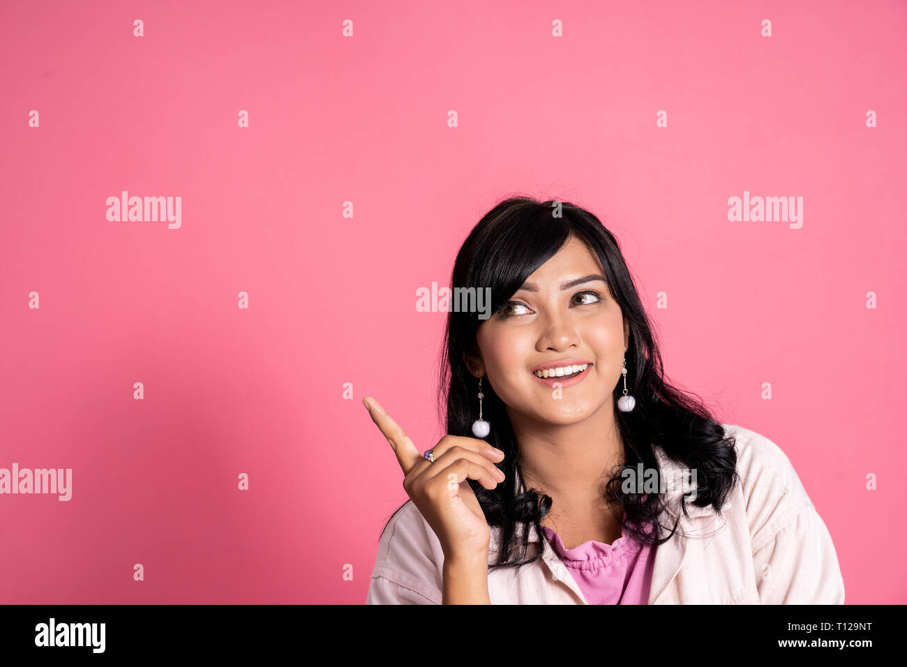casual young woman thinking and pointing up to copyspace - Stock Image