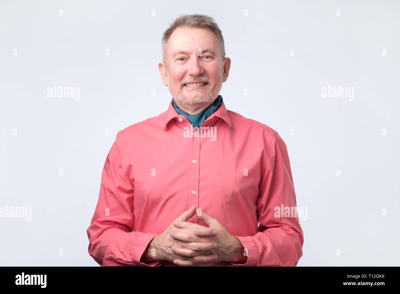 Senior man laughing in red shirt. Studio shoot - Stock Image