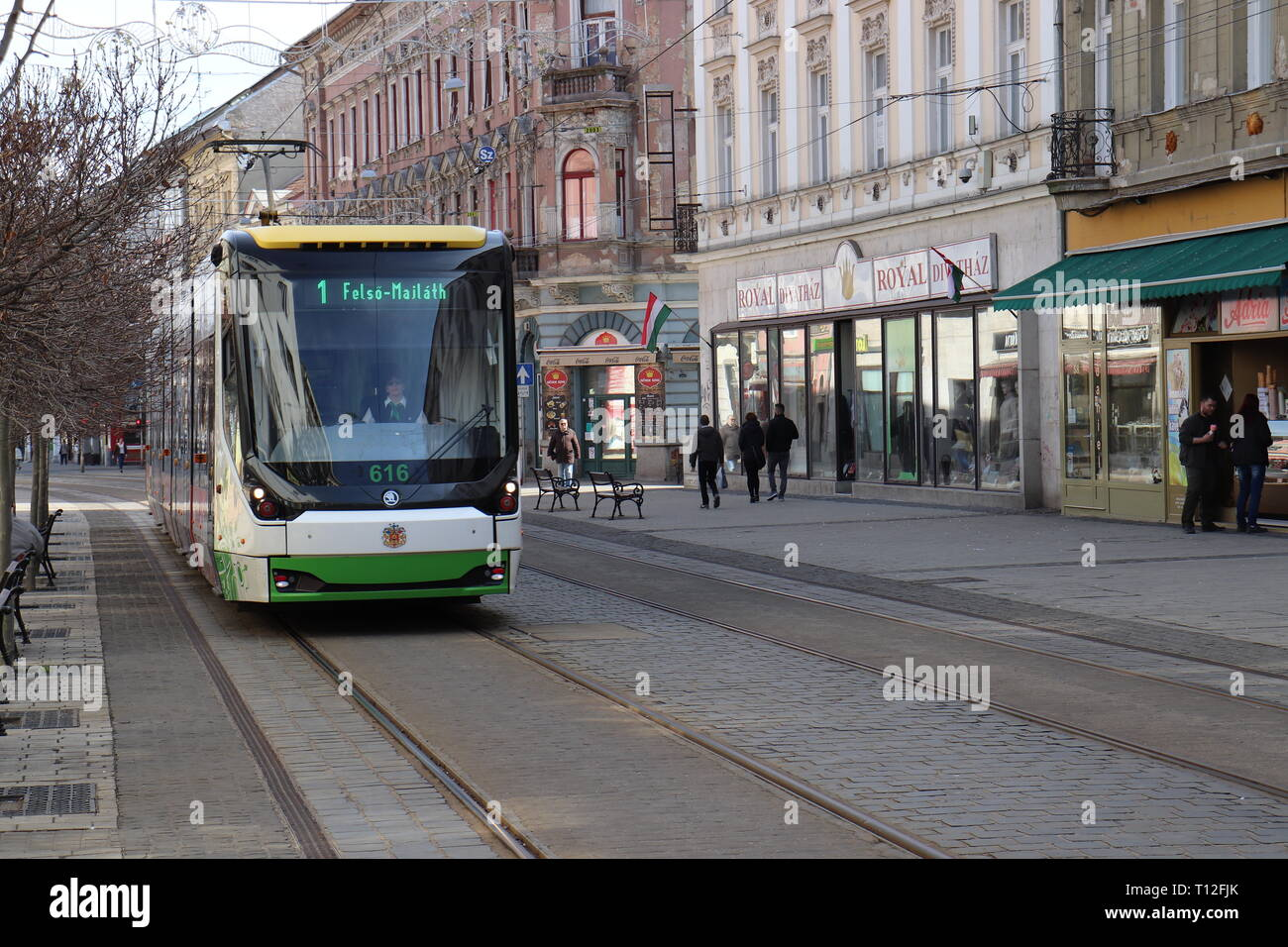 Street moments in Miskolc, Hungary with tram and old buildings. Pedestrian zone with public transport. Stock Photo
