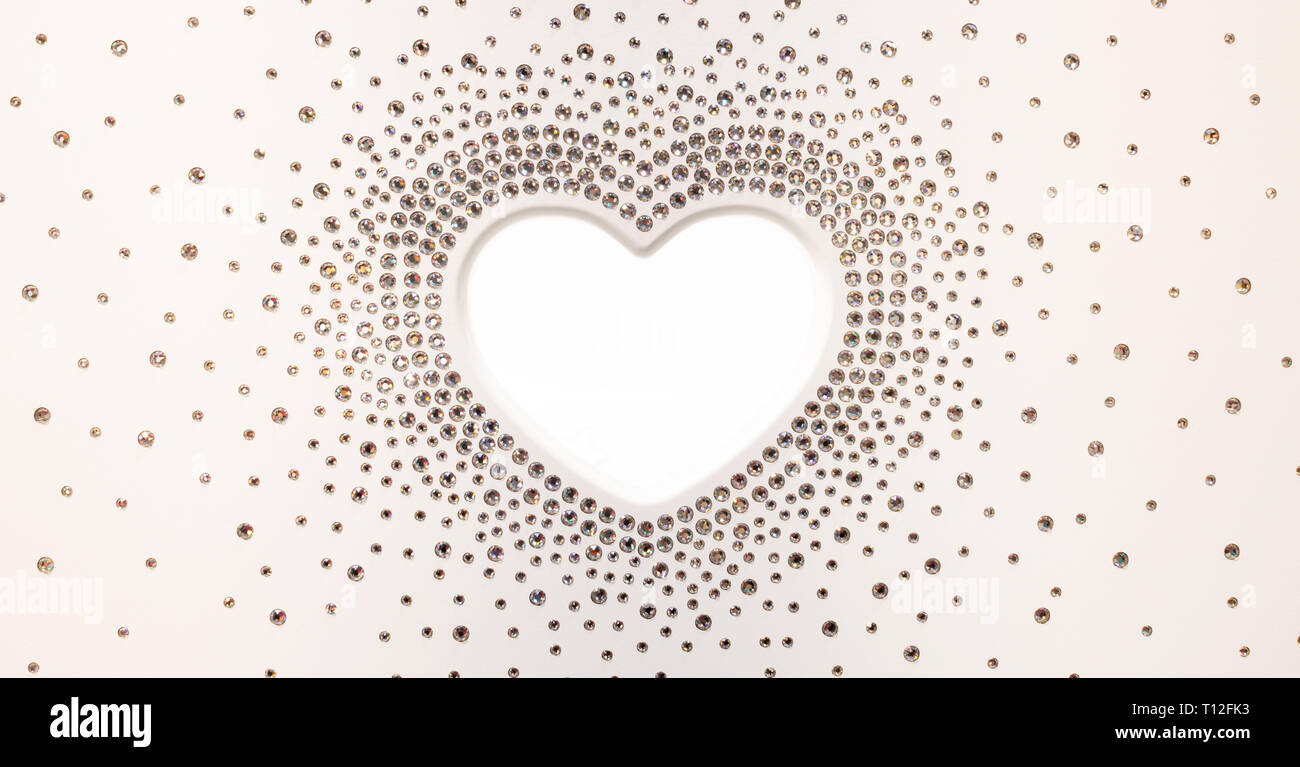 The shape of white heart with crystals around as shiny diamonds Stock Photo