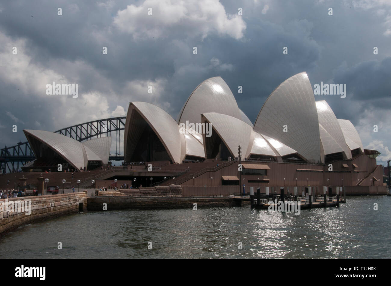 Sydney Opera House, with the Harbour Bridge beyond, against a stormy sky, Sydney, Australia Stock Photo