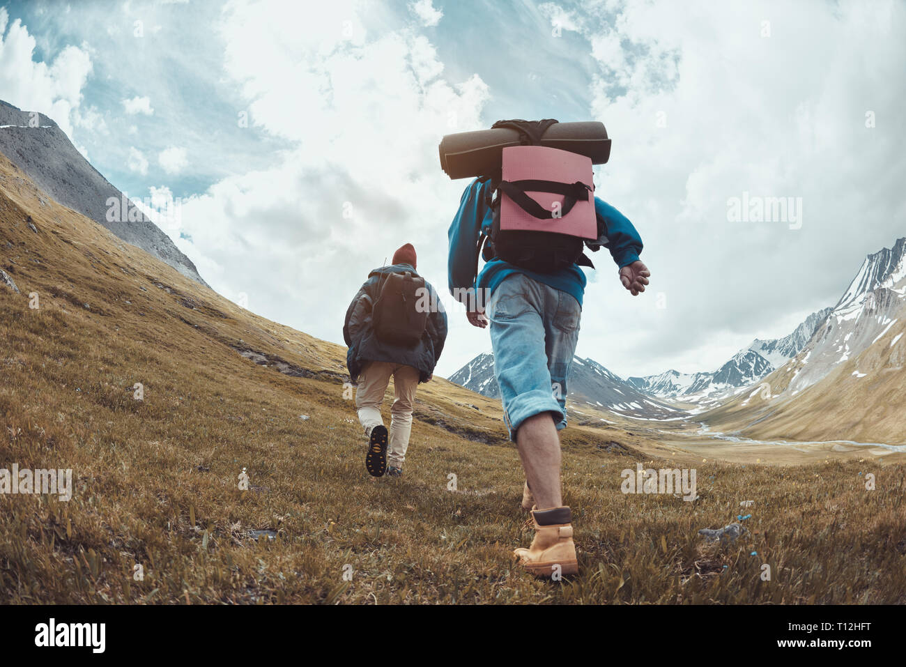 Two hikers in casual clothes and backpacks goes uphill in mountains Stock Photo