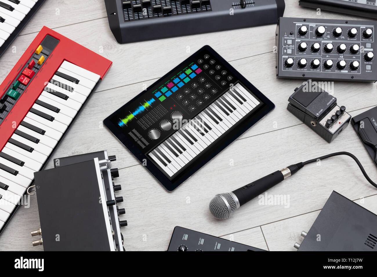 Piano synthesizer app on tablet and musical instrument concept  - Stock Image