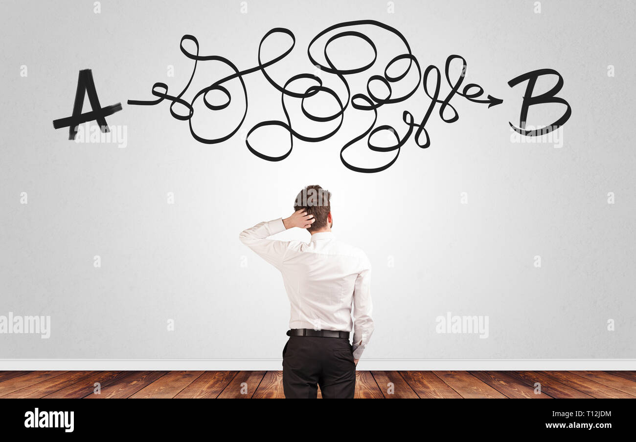 Businessman looking for connection between two things while standing in front of a wall  - Stock Image