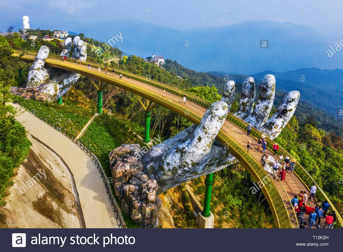 Aerial view of the Golden Bridge is lifted by two giant hands in the tourist resort on Ba Na Hill in Danang, Vietnam. Ba Na famous mountain - Stock Image