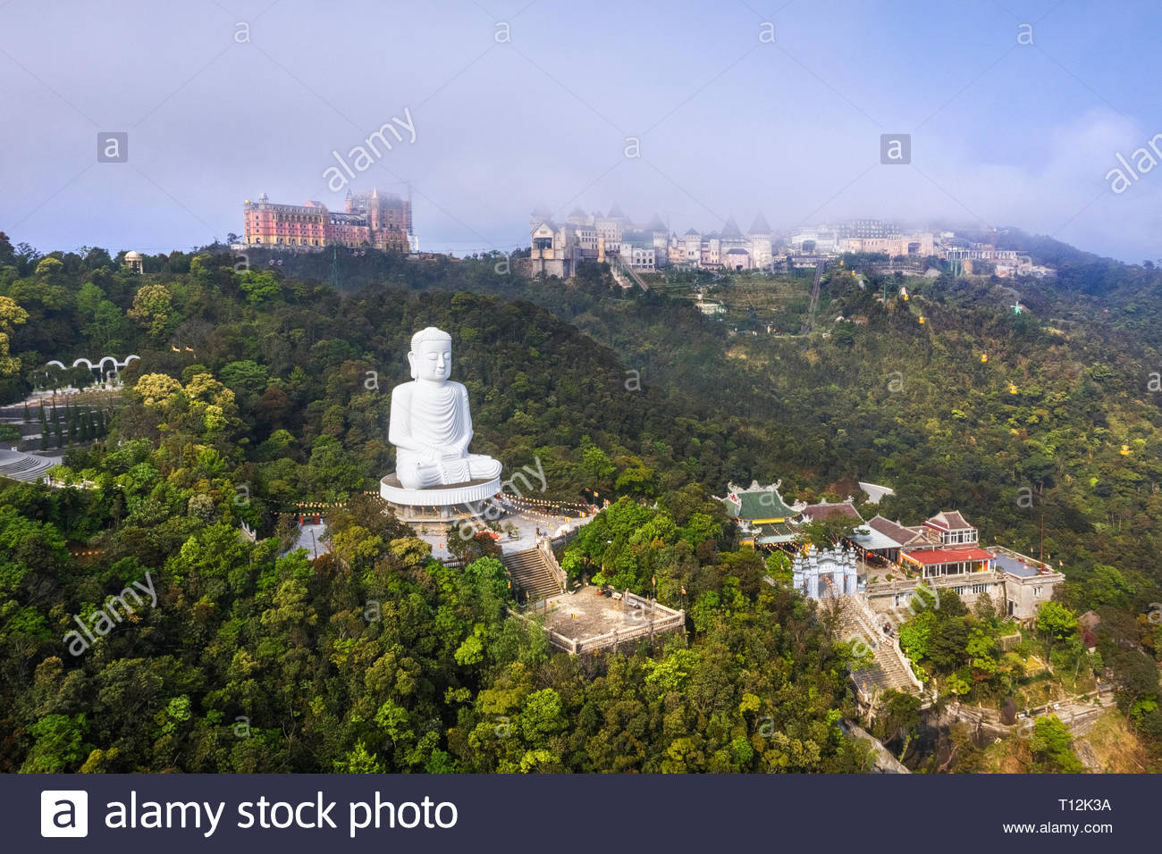 Aerial view of Linh Ung Pagoda with a giant buddha statue among green trees and sea clouds floating on the top of Ba Na mountain, Da Nang, Vietnam - Stock Image