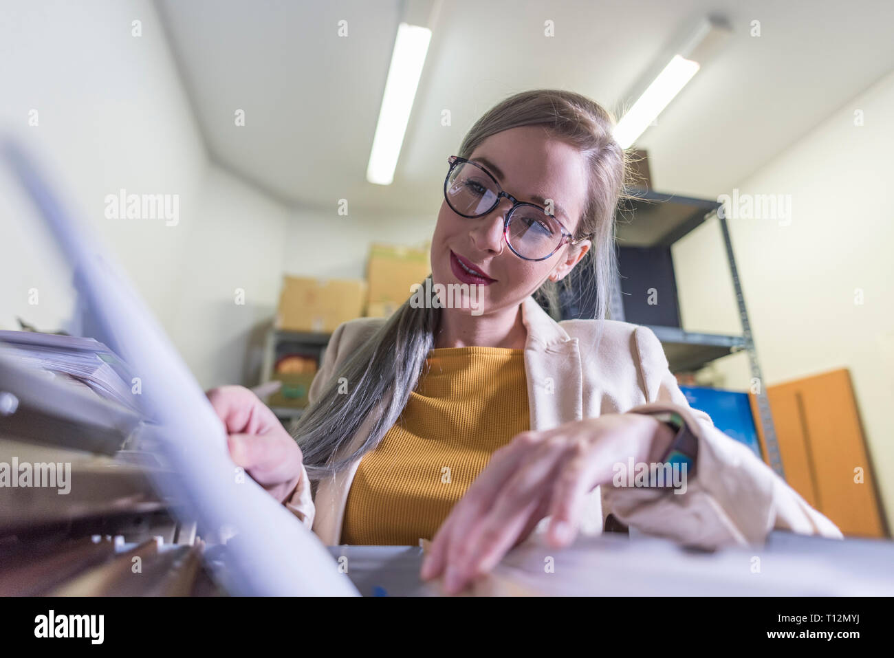 wide angle of attractive office woman working looking files in basement - Stock Image
