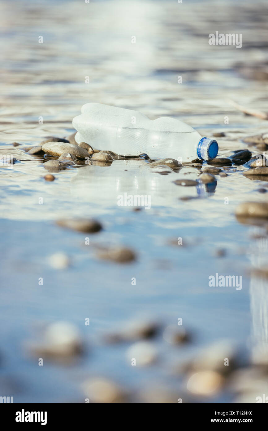 Plastic bottle is lying on the stony beach, environmental pollution - Stock Image