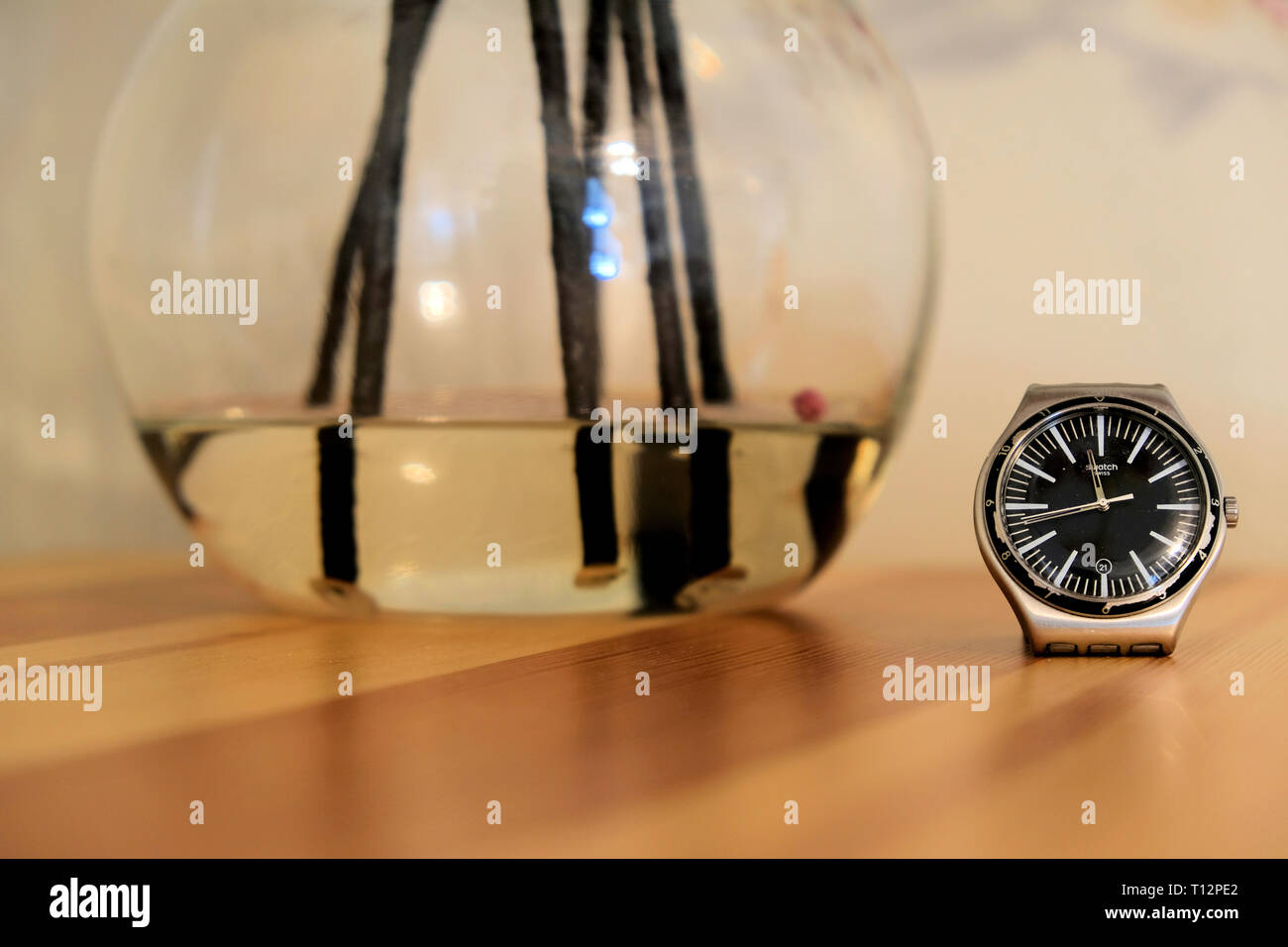 Wrist watch on wooden counter top with flower vase base with water and artificial flower stems; concept or order and time. - Stock Image