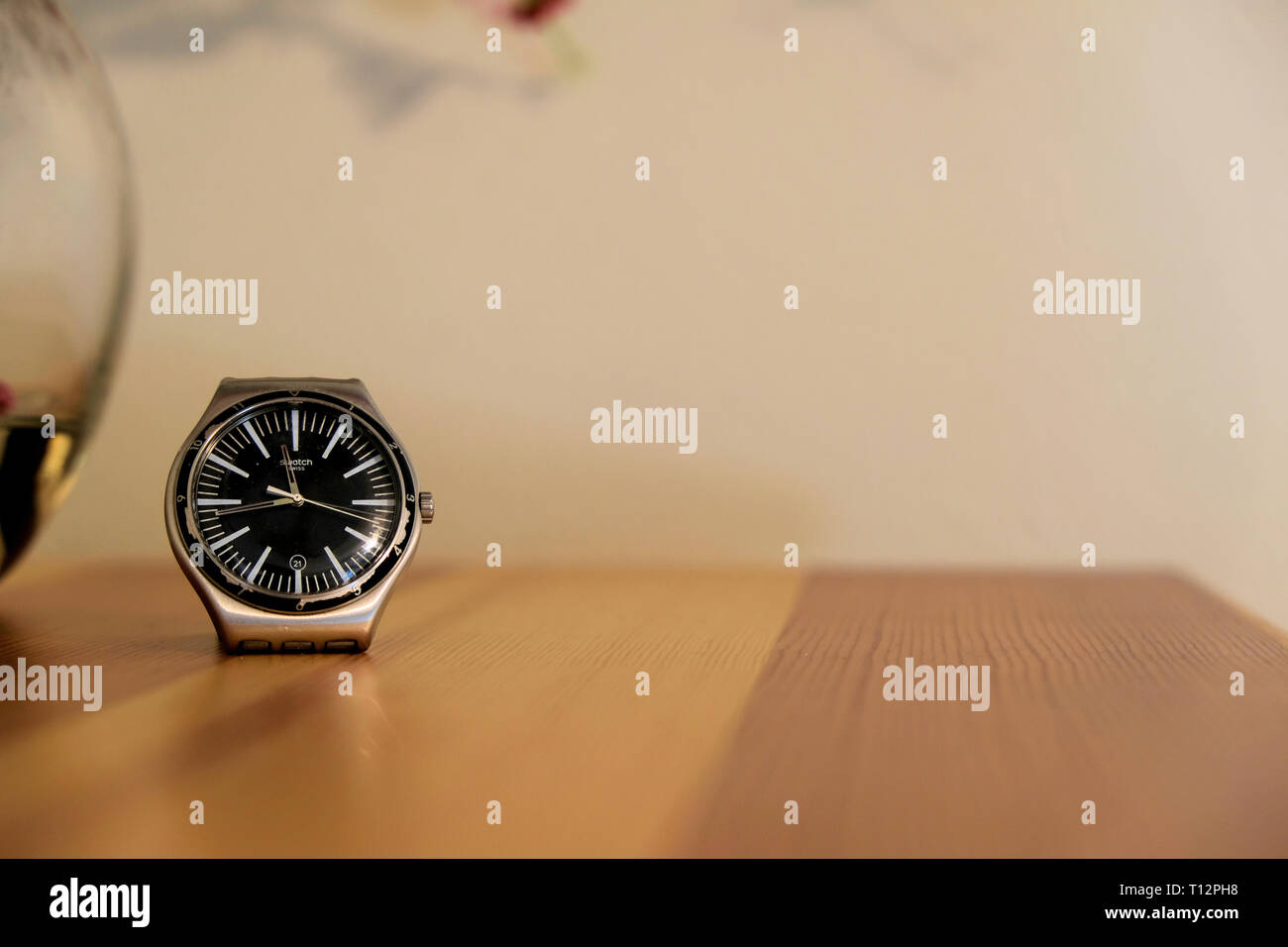 Wrist watch on wooden counter top; concept or order and time. - Stock Image