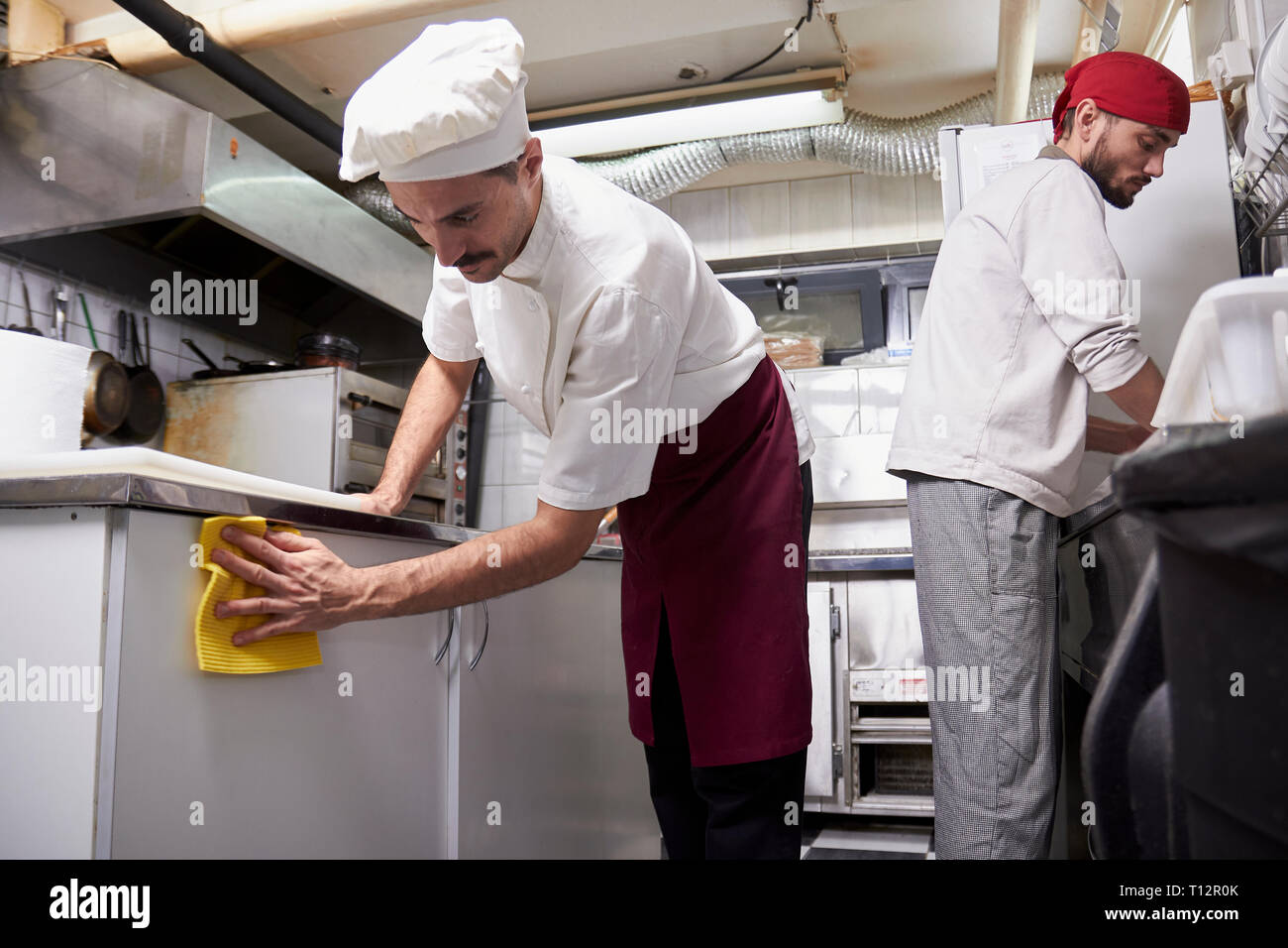 Two People Young Chef In Kitchen Cleaning Cabinets After Closing Restaurant Stock Photo Alamy